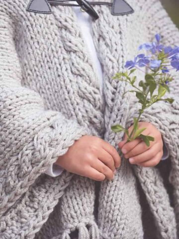child holding flowers in knit cape