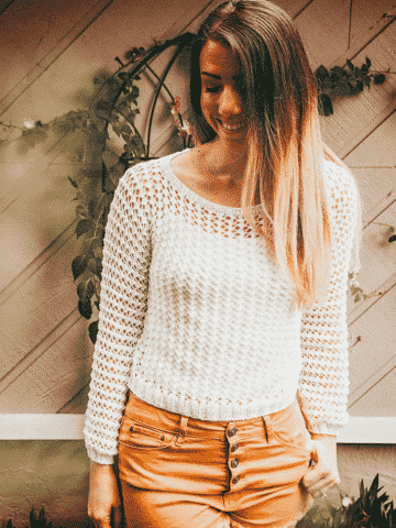 A girl standing in front of vines and flowers. She is wearing a white knit lace sweater with yellow shorts.
