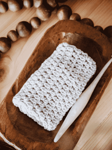 a rolled up yarn washcloth in a wood tray with a crochet hook and decorative beads