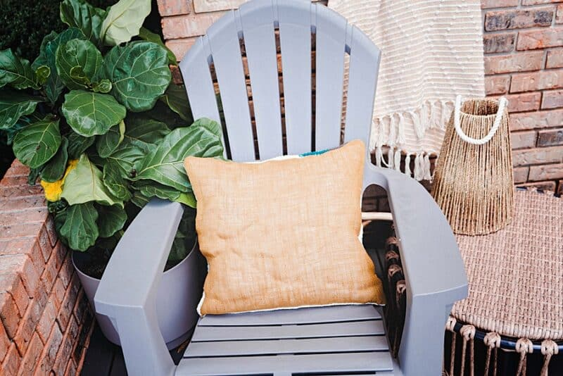 A pillow sitting on a chair next to a plant. Yarn is the pillow burlap.