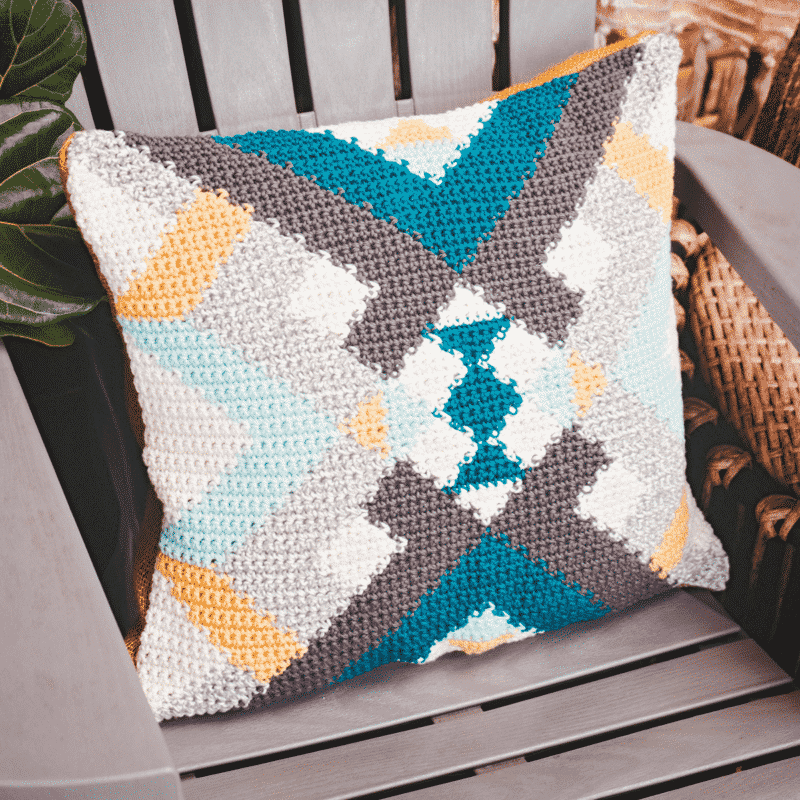 A pillow sitting on a chair next to a plant. Yarn is the pillow fabric.
