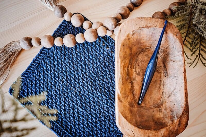 A blue crochet washcloth next to a wood bowl containing a crochet hook and decorative beads.