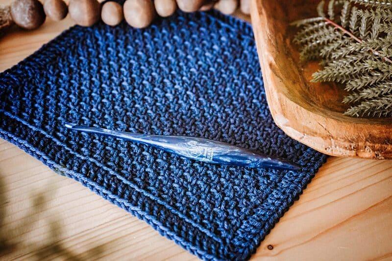 a textured blue crochet fabric and crochet hook