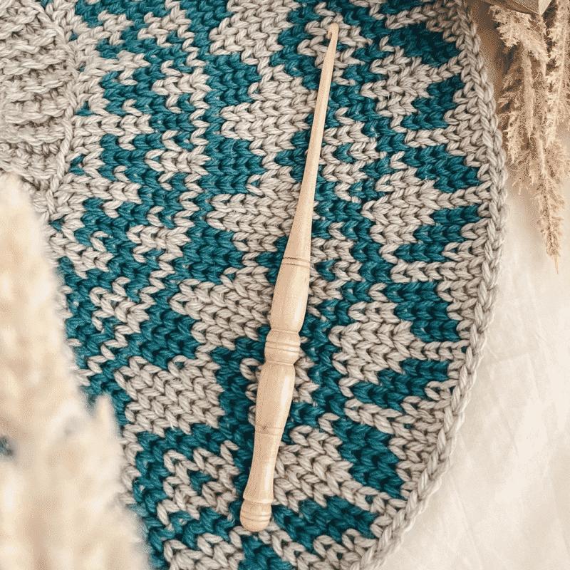 A crochet hook in a colorwork yoke